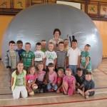 Dzieci biorące udział w prezentacji multimedialnej na tle planetarium.